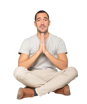 ジェスチャーを祈る幸せな若い男