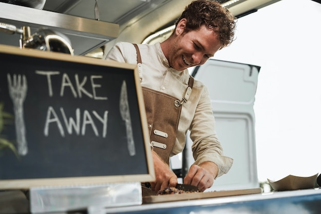 Happy young man preparing take away food inside food truck - focus on man face
