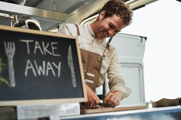 푸드트럭 안에서 음식을 테이크아웃할 준비를 하는 행복한 청년 - 남자 얼굴에 초점