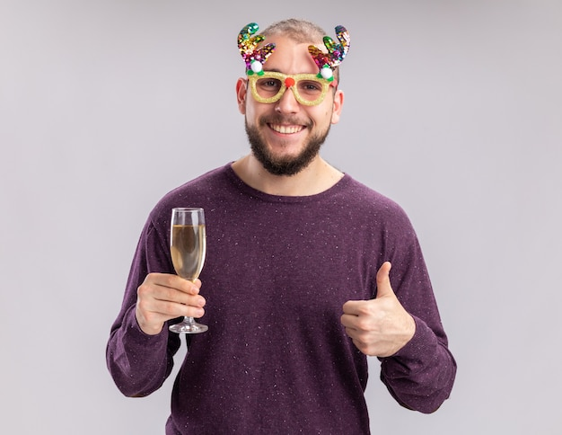 Happy young man in purple sweater and funny glasses holding glass of champagne looking at camera with smile on face shoeing thumbs up standing over white background