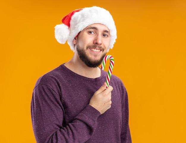 Felice giovane uomo in maglione viola e santa hat tenendo il bastoncino di zucchero guardando la fotocamera con il sorriso sul viso in piedi su sfondo arancione