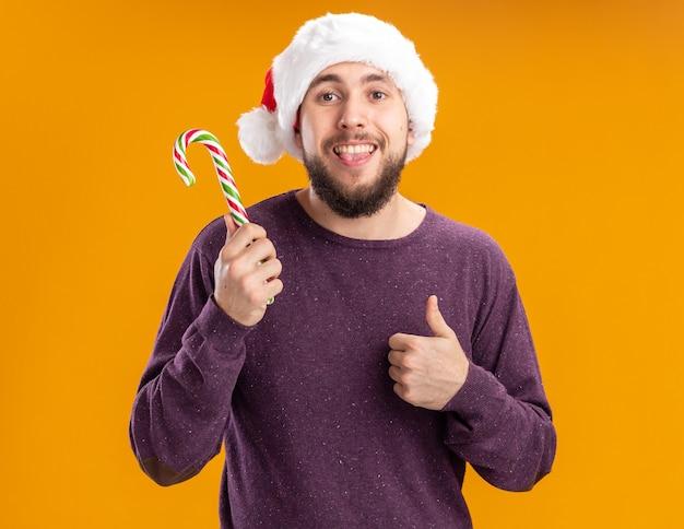 Felice giovane uomo in maglione viola e santa hat tenendo il bastoncino di zucchero sporgente lingua che mostra i pollici in su in piedi su sfondo arancione