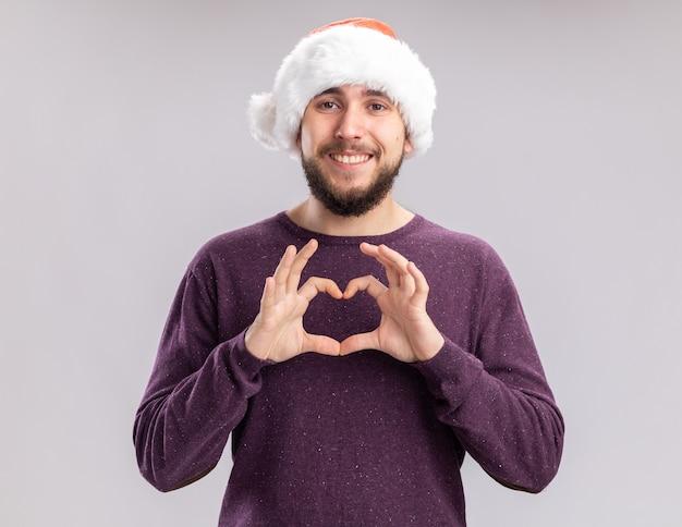 Felice giovane uomo in maglione viola e santa hat guardando la telecamera facendo il gesto del cuore con le dita sorridendo allegramente in piedi su sfondo bianco