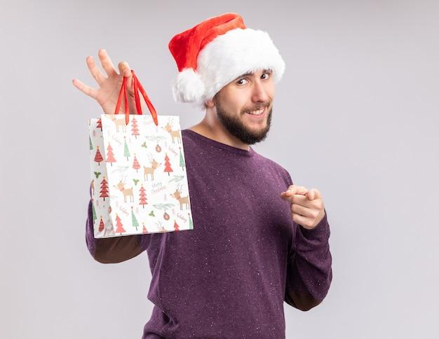 Felice giovane uomo in maglione viola e cappello da babbo natale che mostra un sacchetto di carta regalo che punta con il dito indice alla telecamera sorridendo allegramente in piedi su sfondo bianco