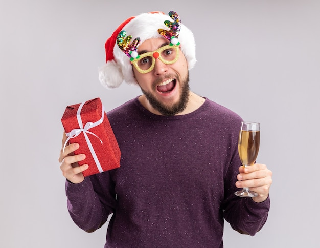 Happy young man in purple sweater and santa hat wearing funny glasses holding glass of champagne and present