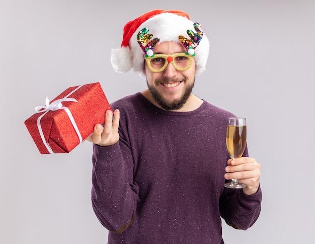 Felice giovane uomo in maglione viola e santa hat indossando occhiali divertenti tenendo un bicchiere di champagne e presente