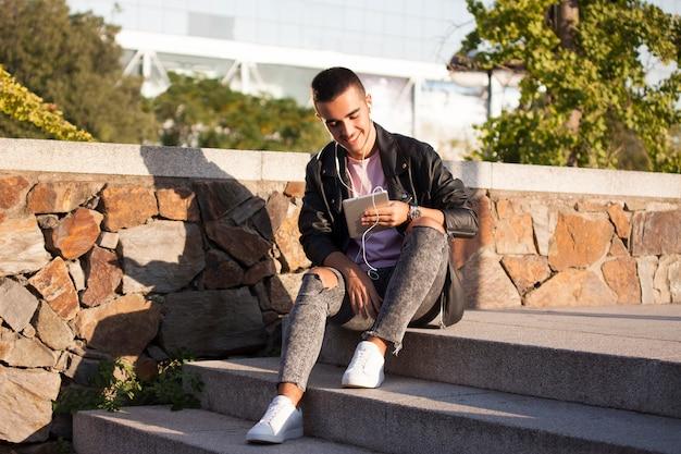 幸せな若い男がタブレットで読んだり、階段で音楽を聴いたり