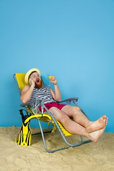 Happy young man resting, takes selfie, drinking cocktails on blue  space