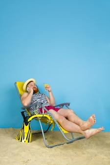 Felice giovane uomo che riposa, prende selfie, bevendo cocktail su sfondo blu studio. concetto di emozioni umane, espressione facciale, vacanze estive o fine settimana. freddo, estate, mare, oceano, alcol.