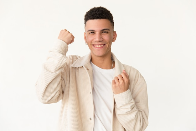 Happy young man shaking fists