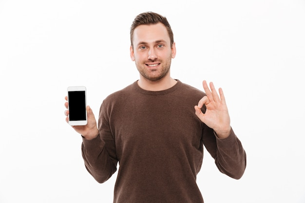 Happy young man showing display of mobile phone