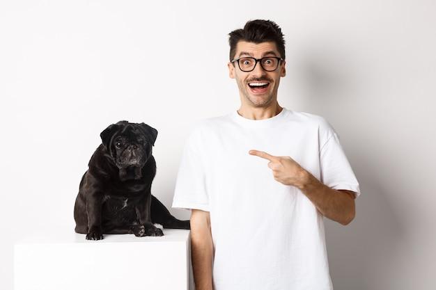 Счастливый молодой человек показывает свою милую собаку, указывая пальцем на черного мопса и улыбается, стоя на белом фоне