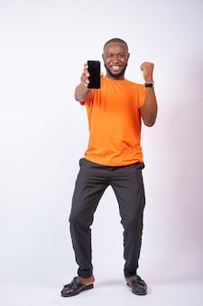 白い背景で隔離の彼の電話画面を示す幸せな若い男