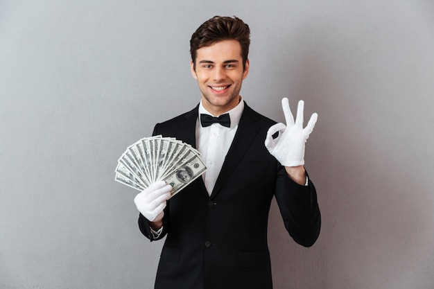 Happy young man showing okay gesture holding money.