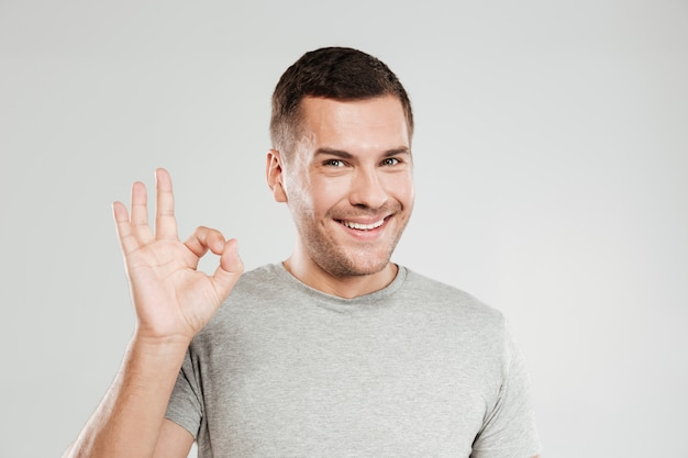 Happy young man showing okay gesture.