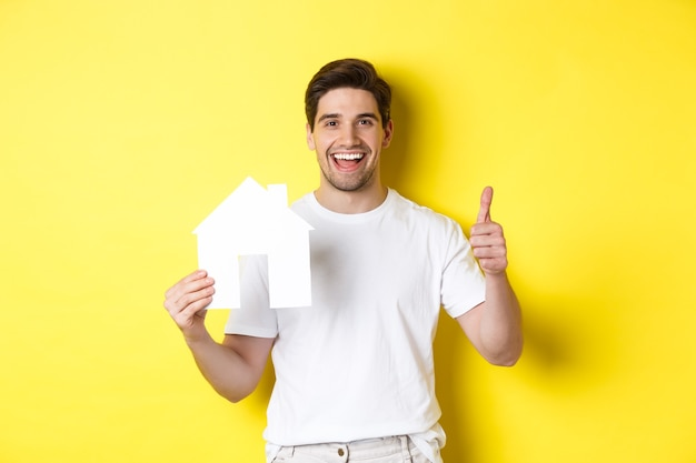 Happy young man showing paper house model and thumbs up, recommending broker, standing over yellow wall