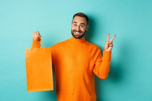 평화 서명 및 오렌지 쇼핑 가방을 보여주는 행복 한 젊은 남자 기쁘게 웃 고, 청록색 배경 위에 서. 공간 복사