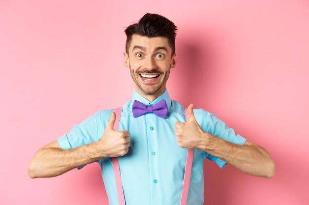 Счастливый молодой человек показывает палец вверх и улыбается, говорит да, согласен с чем-то крутым, рекомендует отличную сделку, оптимистично стоя на розовом фоне.