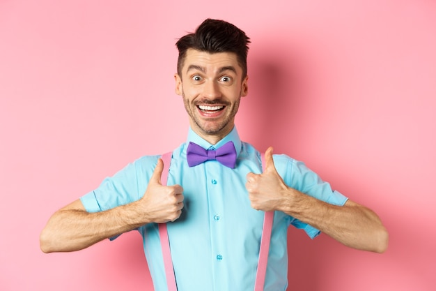 Happy young man showing thumbs up and smiling, saying yes, agree with something cool, recommending excellent deal, standing upbeat on pink background.