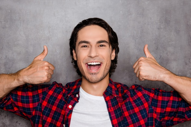 Happy young man  showing thumbs up and smiling