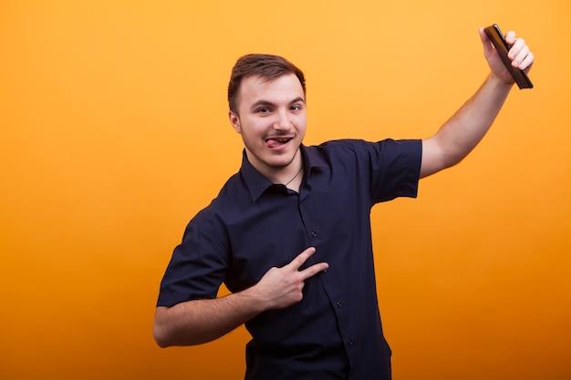 勝利のサインを示し、黄色のバックラウンドで携帯電話を保持している幸せな若い男。面白い若い男