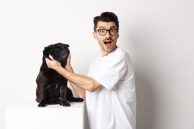 Giovane felice che ti mostra il viso carino del suo carlino. proprietario del cane che ama il suo animale domestico, in piedi su sfondo bianco.