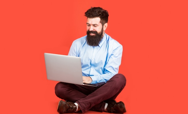 Happy young man sitting on the floor with and using laptop computer on red background.