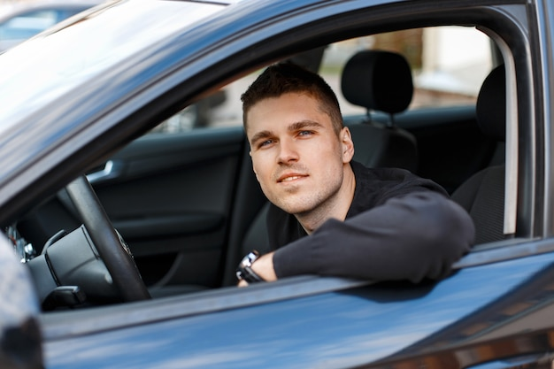 검은 차에 앉아 행복 한 젊은 사람