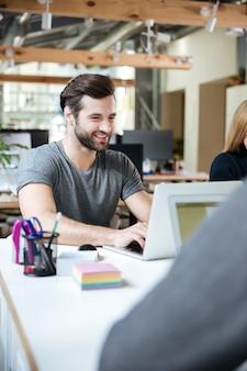 사무실 coworking에 앉아 행복 한 젊은 사람