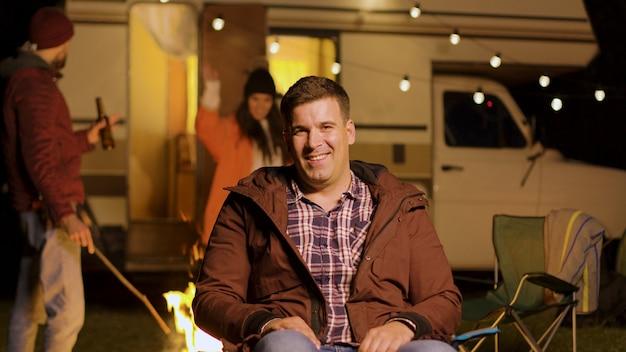 秋の寒い夜にカメラを見ながらキャンプチェアに座って幸せな若い男。レトロなキャンピングカー。