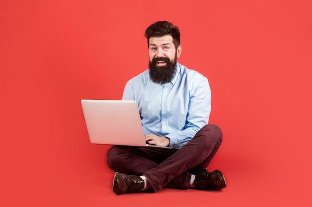 Счастливый молодой человек сидит на полу с ноутбуком и использует его