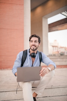 Happy young man sitting on staircase with laptop