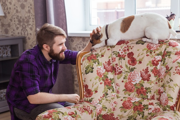 Happy young man sitting with his dog at home. pet owner, animals and friendship concept.