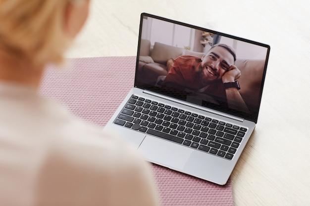 Счастливый молодой человек улыбается с монитора ноутбука женщине, которую они разговаривают в интернете