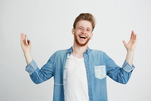 ヘッドフォンの歌でストリーミング音楽を聴いて笑って幸せな若い男。