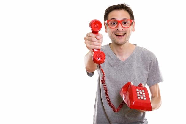 古い電話を与えながら笑って幸せな若い男
