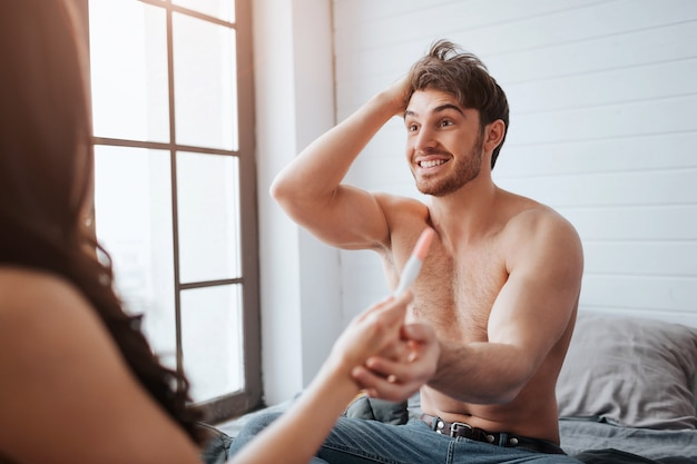 Happy young man smiling to woman. they sit on bed in room at window. guy cheering. he hold woman's hand with positive pregnancy test result.