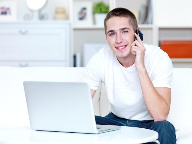 행복한 젊은 남자가 전화로 말하고 집에서 노트북에서 작동합니다.