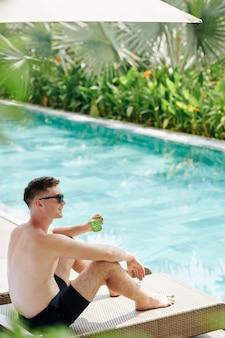 수영장에서 화창한 날을 보내고 차가운 칵테일을 마시는 행복한 젊은 남자