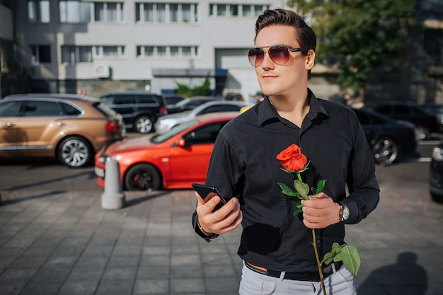 Happy young man stand and smile. he hold phone and red rose in hands. there are road with cars behind. it is sunny outside.
