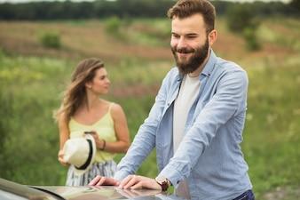 車の近くの女性の前に立っている幸せな若い男