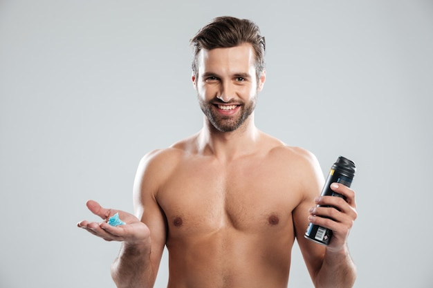 Happy young man standing isolated holding shaving foam