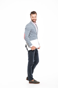 Happy young man standing isolated laptop computer