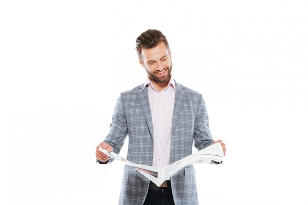 Happy young man standing isolated reading gazette