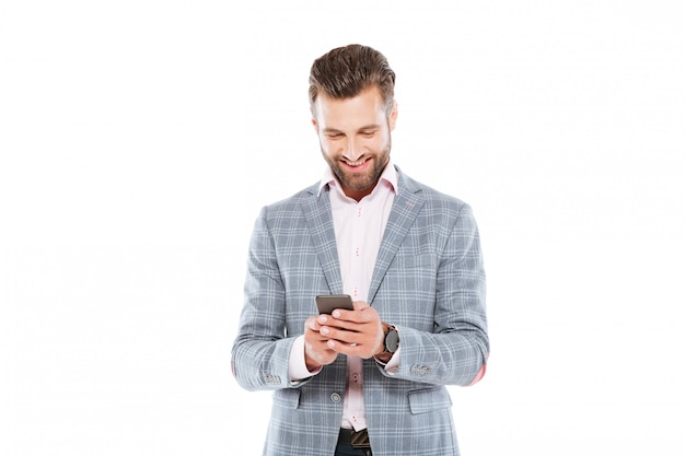 Happy young man standing isolated using mobile phone.