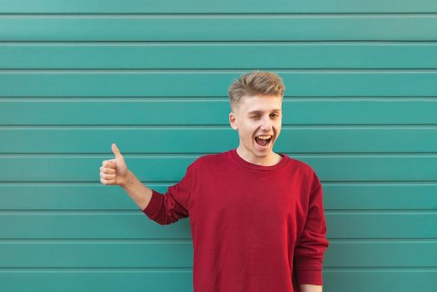 ターコイズの上に立って、親指を現して幸せな若い男。