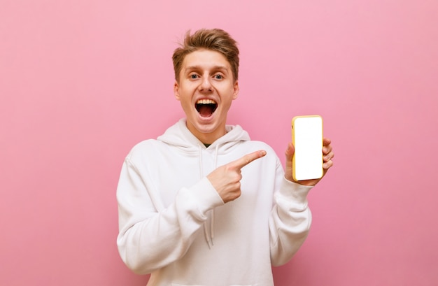 Happy young man standing on pink background with smartphone in hand on pink background looking into camera with surprised face and showing finger on black screen.