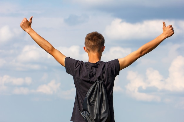 Happy young man standing on top with his hands up