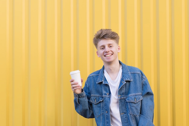 Happy young man standing with a cup of coffee on a yellow wall and smiling.