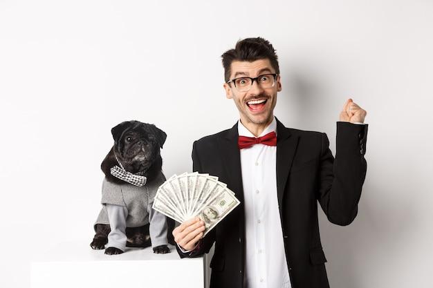 Il giovane felice in vestito guadagna soldi con il suo cane. ragazzo che si rallegra, tiene in mano dollari, carlino nero in costume che fissa la telecamera, sfondo bianco.